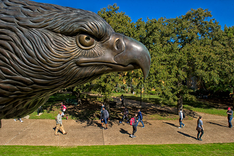 Students walking past eagle statue
