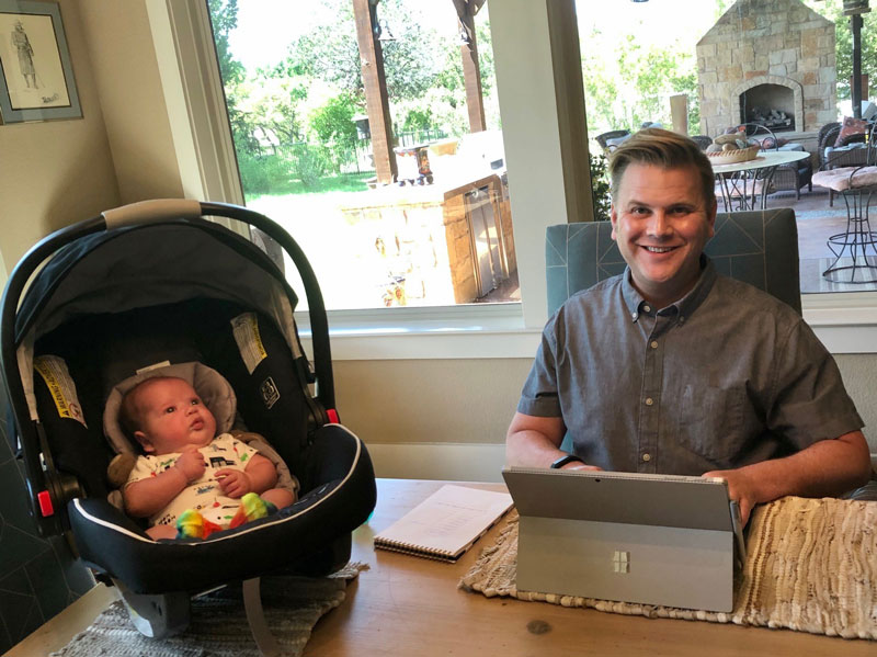 Ryan Boettger working at home with his newborn