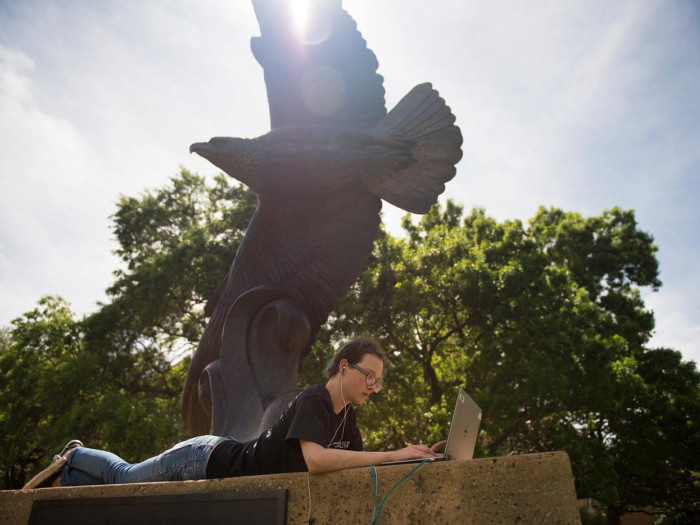 Student studying at base of eagle statue