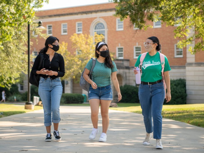 UNT students wearing masks and walking on campus